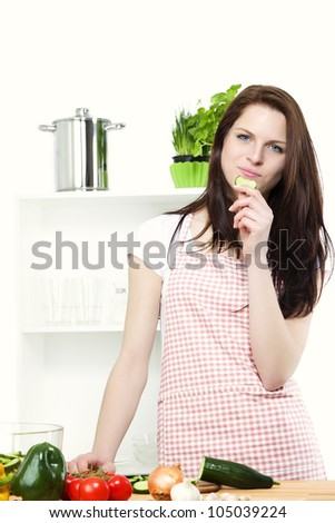 positive young woman standing in a kitchen with vegetables nibbling on a cucumber - stock photo