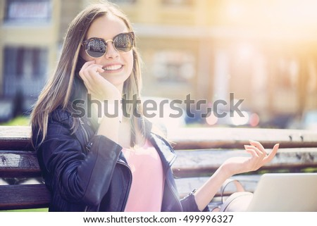 Positive young woman talkign on smart phone