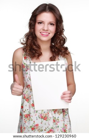 Positive young woman wearing clothes with floral ornament and showing white blank card - stock photo