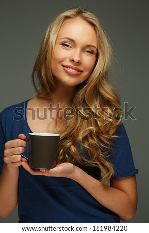 Positive young woman with long hair and blue eyes holding cup - stock photo