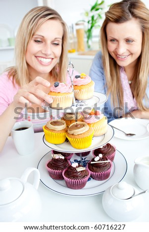 Positive young women eating cakes in the kitchen at home - stock photo