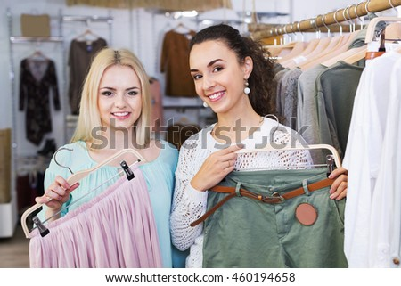 Positive young women shopping at the clothing store