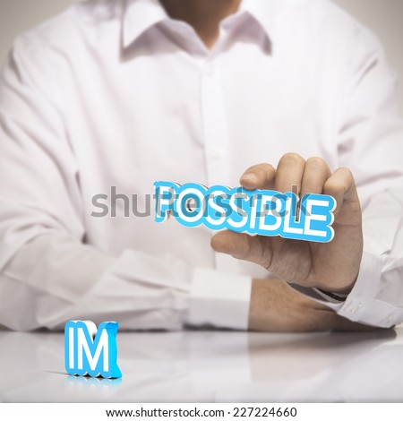 Possible versus impossible concept of motivation. One man holding the word possible in one hand with  the prefix   - stock photo