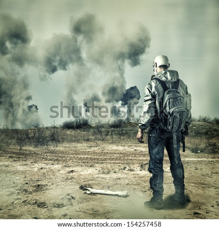 Post apocalypse. Man in gas mask with handgun and  back pack in apocalyptic world looking on explosions on horizon - stock photo