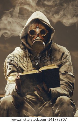 Post apocalyptic survivor in gas mask reading a book