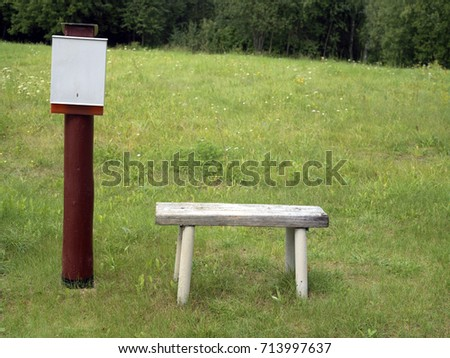 Post box and wooden bench in the open field, a forest in the background