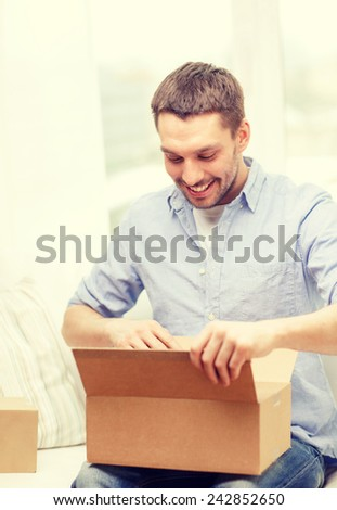post, home and lifestyle concept - smiling man with cardboard boxes at home - stock photo