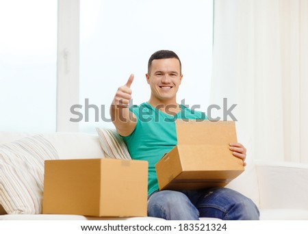 post, home and lifestyle concept - smiling man with cardboard boxes at home showing thumbs up - stock photo