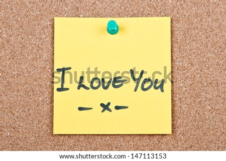Post it note on wood in yellow with I love you