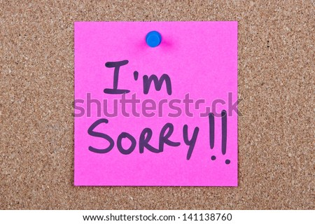 Post it note pink with i'm sorry message on cork