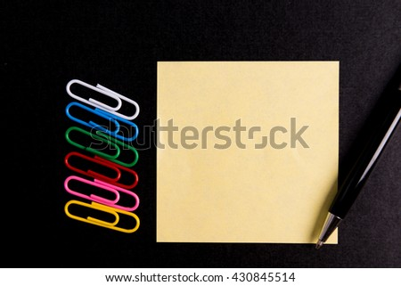 post it paper note  with Paper clip and pen on black paper - stock photo