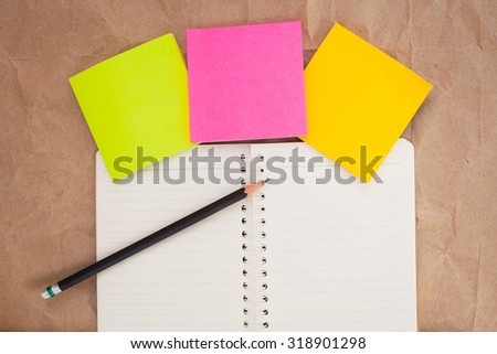 post it, pencil and notebook on brown paper background - stock photo