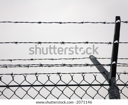 Post of a chain-link fence topped with barbed wire.