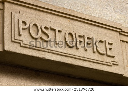 Post Office Building entrance carved in stone above the door of the postal service - stock photo