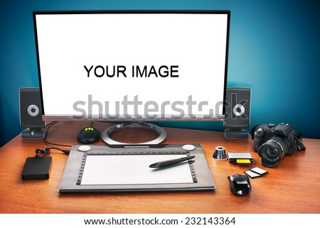 Post production desk with digital camera, memory cards, graphic tablet, and monitor to advertise youself and your work. Blank monitor to paste your image. - stock photo