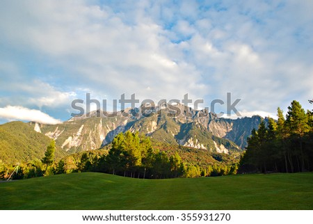 Post quake view of majestic Mount Kinabalu from maintained green lawn at Mesilau, Ranau, Sabah during a beautiful morning.  - stock photo