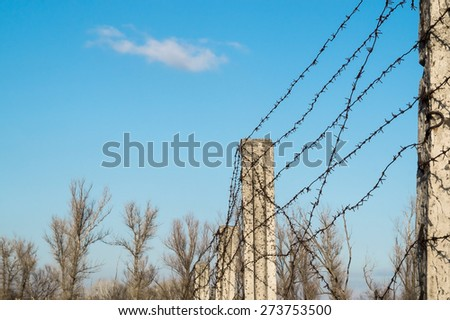 post with barbed wire against the sky - stock photo