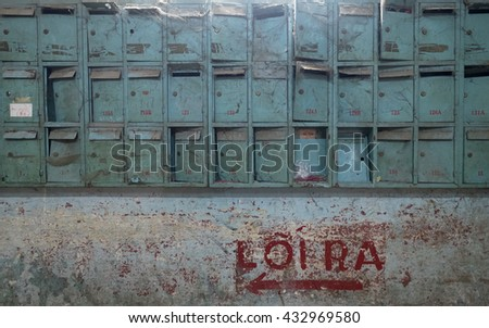 Postage mail boxes in one of oldest apartment, built since 1960s by French, include 6 blocks going down, suppose to destroy, build up the new one. The bottom red letters with arrow means the exit way. - stock photo
