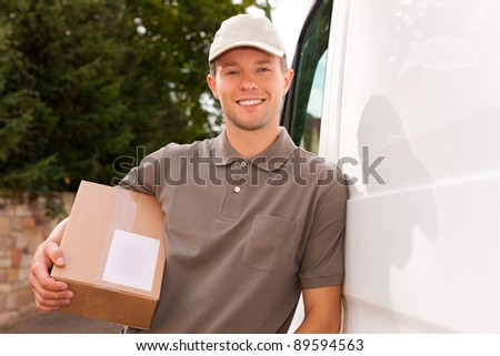Postal service - delivery of a package through a delivery service; the postman is leaning on his van - stock photo