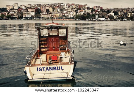 Postcard from Istanbul. Motor boat by the Golden Horn - Istanbul, Turkey. The Beyoglu district in the background.
