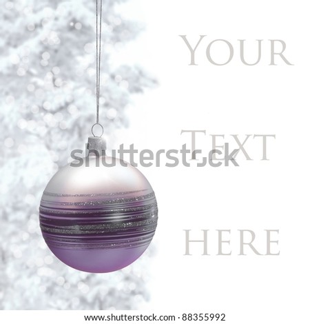 Postcard with Christmas bauble and snowy pine. Space for text on right.? - stock photo