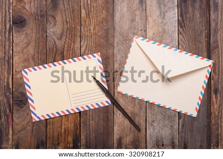 Postcard with fountain pen end envelope on old wooden table