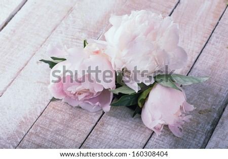 Postcard with fresh flowers peony on wooden background. Toned. - stock photo