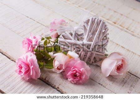 Postcard with fresh roses and white decorative heart on wooden background. Selective focus. - stock photo