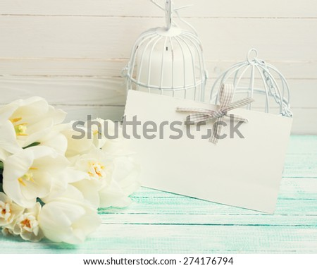 Postcard with fresh spring flowers  tulips and daffodils and empty tag for your text on turquoise painted planks against white wall. Selective focus. Toned image. - stock photo