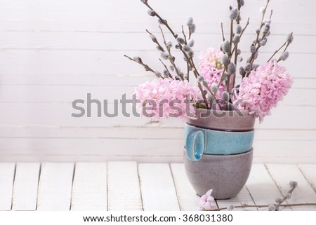 Postcard with hyacinths and willow flowers in vase on white wooden background. Selective focus. Place for text. - stock photo
