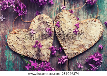Postcard with two decorative hearts and fresh lilac flowers on green aged wooden background. Selective focus. Toned image. - stock photo