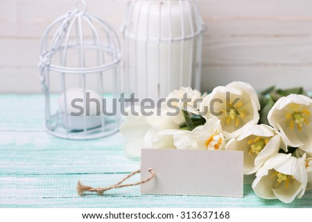 Postcard with white  flowers  tulips and daffodils and empty tag for your text on turquoise painted planks against white wall. Selective focus. - stock photo