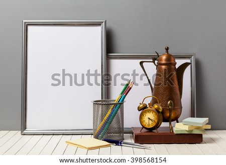 poster frame with office details and an alarm clock with a coffee pot on a wooden table - stock photo