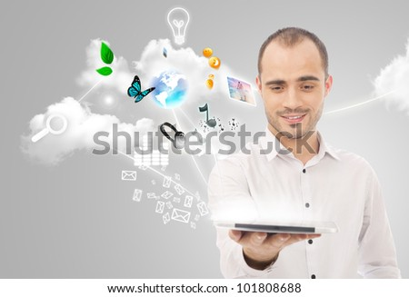 Poster portrait of handsome man holding his universal device - tablet pc. Lots of things are appearing from the display. Universality of modern devices concept - stock photo