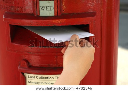 posting a letter to red british postbox on street - stock photo