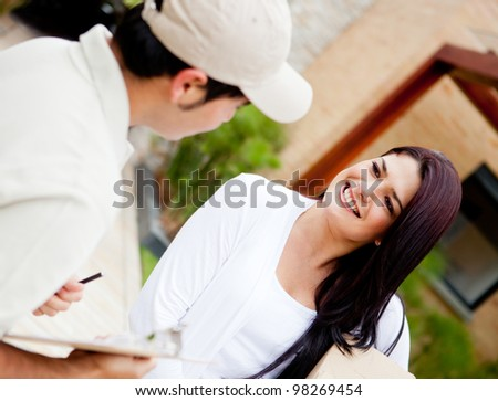 Postman delivering a package to a woman at home - stock photo