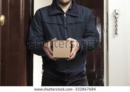 Postman delivers a small package - stock photo