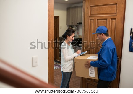 Postman waiting when woman signing delivery document on the digital tablet - stock photo