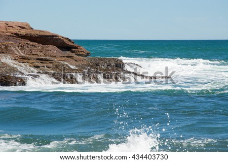 Pot Alley coast line with red sandstone outcroppings and Indian Ocean waters cascading over the rock  in Kalbarri, Western Australia/Cascading Water/Pot Alley, Kalbarri, Western Australia - stock photo