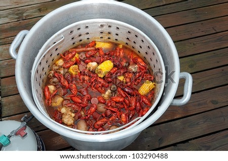 Pot And Basket Of Hot Boiled Louisiana Crawfish With Potatoes,Corn, Garlic, Mushrooms  And Sausage - stock photo