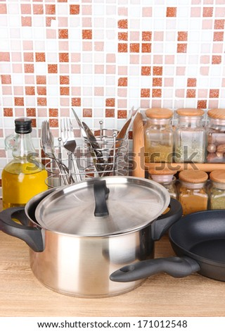 Pot and pan in kitchen on table on mosaic tiles background - stock photo