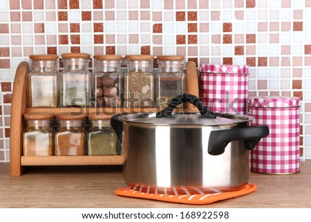 Pot and spices in kitchen on table on mosaic tiles background