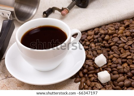 pot, grinder and cup of coffee on sacking - stock photo