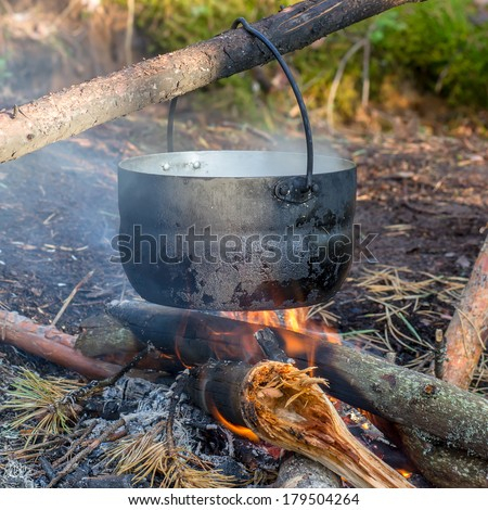Pot Hanging Over The Fire In The Forest In A Hike The