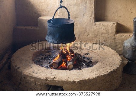 pot hanging over the fire in the hearth - stock photo