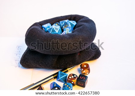 Pot of Dice in a cloth style bag, showing the gamers life overloaded with tons of dice in his collection. The purpose is to visualize traditional board games and roleplaying games.
