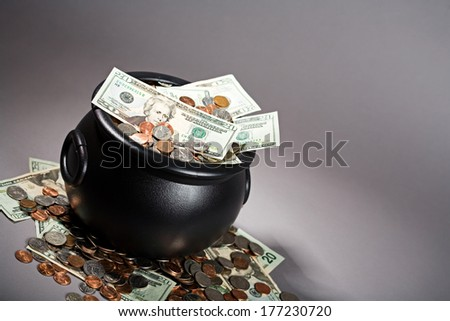 Pot Of Gold: Cauldron of US Cash and Coins on Grey