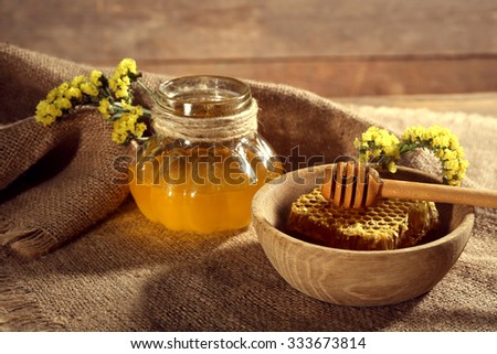 Pot of honey, honeycomb and dipper in bowl on sacking on wooden background - stock photo