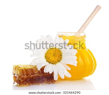 Pot of honey with wooden dipper, honeycomb and chamomile isolated on white - stock photo