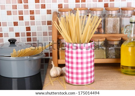 Pot on stove in kitchen on table on mosaic tiles background - stock photo